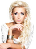 Schöne blonde Frau mit langem gelocktes Haar- und Artmake-up Stockfoto