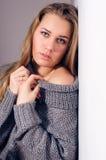 Schöne blonde junge Frau, die Kamera in den Strickwaren betrachtet Stockfotos