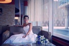 Schöne Braut, die an einem Innencafé sitzt Stockbilder