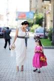 Schöne Braut, die zusammen mit flowergirl aufwirft Lizenzfreie Stockfotos