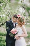 Schöne Braut in einem Hochzeitskleid mit Blumenstrauß und Rosen winden die Aufstellung mit tragendem Hochzeitsanzug des Bräutigam Stockbild