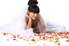 Schöne Braut in einem weißen Kleid mit den rosafarbenen Blumenblättern Stockbild