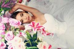 Schöne Braut im eleganten Kleid, das unter Blumen aufwirft Stockbilder