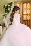 Schöne Braut im eleganten weißen Hochzeitskleid und Schleier mit dem langen gelockten Haar, das zuhause aufwirft Lizenzfreie Stockfotografie