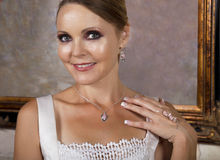 Schöne Braut im Hochzeits-Kleid, das eine Halskette trägt Stockfoto