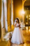 Schöne Braut im Hochzeitskleid, das einen netten Blumenstrauß mit den roten und weißen Rosen aufwerfen nahe Fenster auf Hintergru Stockfotografie