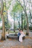 Schöne Braut im silk Hochzeitskleid, das auf Knien ihres liebevollen Bräutigams sitzt Reizend Jungvermähltenpaarrest durch getroc Stockfotografie