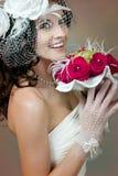 Schöne Braut mit roten Rosen. Stockfoto
