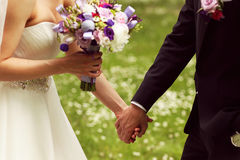 Schöne Brautpaare, die Spaß im Park auf ihrem Hochzeitstagblumenblumenstrauß haben Lizenzfreie Stockfotografie