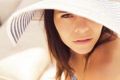 Schöne Brunettefrau auf dem Strand allein, der in einem Hut sich entspannt S Lizenzfreies Stockfoto