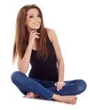 Brunettefrau, die auf dem Boden sitzt. Studiotrieb. Stockfoto