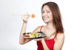 Schöne Brunettefrau, die Sushi isst Stockfotos