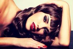 Schöne Brunettefrau mit dem langen gelockten Haar Stockbild