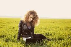 Schöne Dame mit ihrem Laptop auf Gras Lizenzfreie Stockfotos