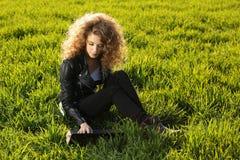 Schöne Dame mit ihrem Laptop auf Gras Stockfotografie