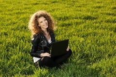 Schöne Dame mit ihrem Laptop auf Gras Stockfoto