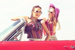 Schöne Damen mit den Sonnenbrillen, die in einem Retro- Auto der Weinlese aufwerfen Stockfotos