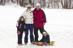 Familie, die Tagschnee sledding genießt Lizenzfreies Stockfoto