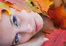 Schöne Frau abgedeckt in den Blättern Lizenzfreie Stockfotos