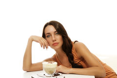 Schöne Frau, die über Cappuccino auf einer Tabelle verbiegt Lizenzfreie Stockbilder
