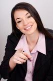 Junge lächelnde Geschäftsfrau, die Finger auf Zuschauer zeigt Stockfoto