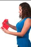 Schöne Frau, die ein Geschenk öffnet Stockbilder