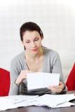 Schöne Frau, die einen Blick an den Dokumenten nimmt. Stockbilder