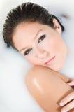 Schöne Frau, die im Milchbad sich entspannt Stockfotos