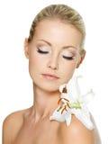 Schöne Frau, die mit weißer Lilie auf Karosserie sich entspannt Lizenzfreie Stockbilder