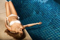 Schöne Frau, die nahe Swimmingpool ein Sonnenbad nimmt Stockfotografie