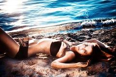 Schöne Frau, die sich auf einem Strand hinlegt Stockfotografie