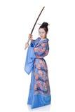 Schöne Frau in einem Kimono mit Samuraiklinge Stockfotografie
