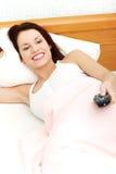 Schöne Frau im Bett, das ein Fernsteuerungs anhält. Lizenzfreies Stockbild