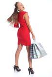 Schöne Frau im roten Kleid hat das Spaßeinkaufen Lizenzfreie Stockbilder