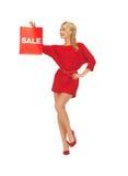 Schöne Frau im roten Kleid mit Einkaufstasche Stockbilder