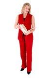Schöne Frau im roten Sleeveless Anzug, der Folde betrachtet Stockfoto