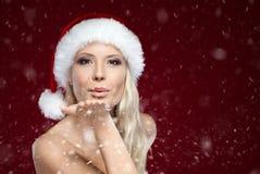 Schöne Frau im Weihnachtsschutzkappen-Schlagkuß Stockbild