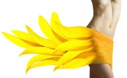 Schöne Frau mit den Sonnenblumeblumenblättern auf ihren Hüften Stockfotos