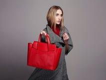 Schöne Frau mit Handtasche Schönheits-Mode-Mädchen im Überzieher Art und Weisefrau mit Beuteln Lizenzfreie Stockfotografie