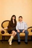 Schöne Frau und junger Mann, die auf Sofa sitzt Lizenzfreie Stockbilder