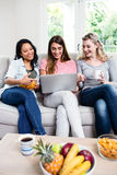 Schöne Freundinnen, die zu Hause im Laptop schauen Stockfotografie