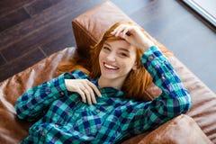 Schöne frohe Frau, die auf braunes Sofa und dem Lachen legt Stockfotografie