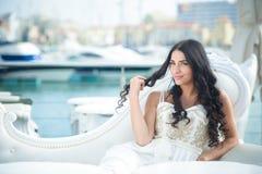 Schöne frohe Frau im eleganten Kleid am sonnigen Tag am Jachthafen Stockfotografie