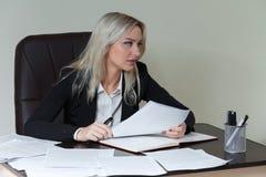 Schöne Geschäftsfrau, die an ihrem Schreibtisch mit Dokumenten arbeitet Stockbilder