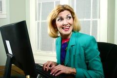 Schöne Geschäftsfrau, die mit Mitarbeitern lacht Lizenzfreie Stockbilder