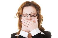Schöne Geschäftsfrau mit den geschlossenen Augen, ihren Mund bedeckend. Stockbild