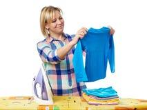 Schöne glückliche Frauenhausfrau, die Wäscherei für das Bügeln hält Lizenzfreies Stockfoto