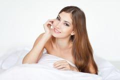Schöne glückliche junge Frau, die auf Bett liegt Lizenzfreie Stockfotos
