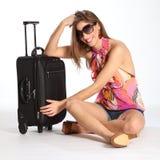 Schöne glückliche junge Frau, die mit Koffer sitzt Stockfotos