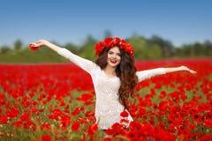 Schöne glückliche lächelnde offene Arme der Frau in der roten Mohnblume fangen natur auf Stockfoto